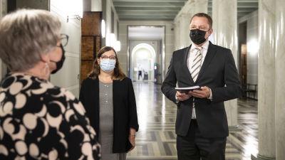 Anu Vehviläinen möter två tjänstemän från revisionsverket, i riksdagens korridor.