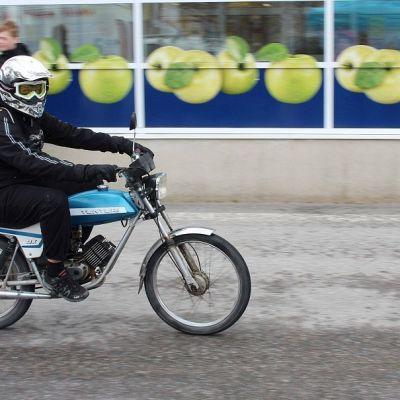 Poika ajaa mopolla Karstulan keskustassa.