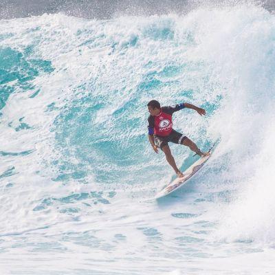 Kuvassa surffaaja, jonka asussa on punaista ja sinistä. Meressä on suuri aalto.