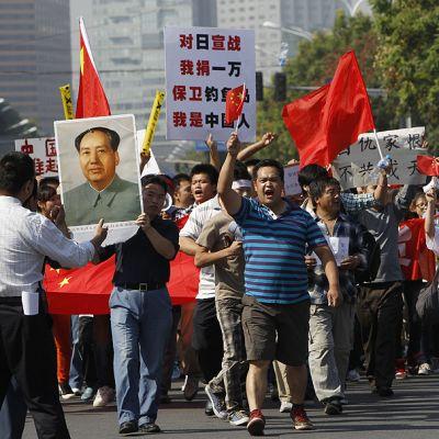 Mielenosoittajat marssivat kadulla.