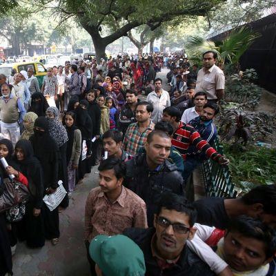 Intialaiset tungeksivat jonoissa pyrkien vaihtamaan vanhoja seteleitään Delhissä.