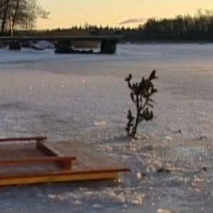 Lucka av trä på en snöig istäkt vik.