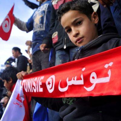 """Pikkupoika pitelee huivia, jossa lukee """"Tunisia"""" ranskaksi ja arabiaksi."""