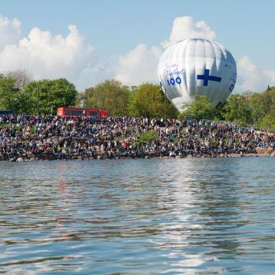 Ihmisiä ja Suomi100-kuumailmapallo Helsingin kaivopuiston rannassa.