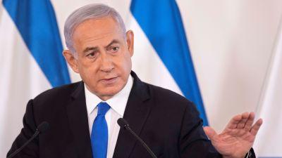 Netanjahu puhuu mikrofoniin. Hänellä on musta puku. valkoinen kauluspaita ja sininen kravatti. Taustalla näkyy Israelin sinivalkoinen lippu.