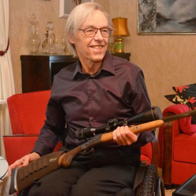 Hannu Laine istuu pyörätuolissa ase sylissään.