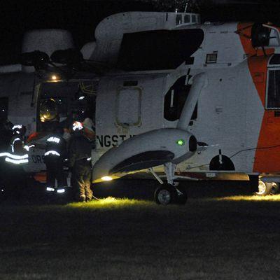 Pelastushenkilökuntaa pelastushelikopterin ovella.