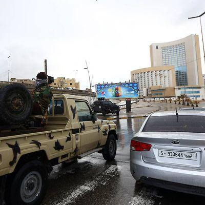 Libyan turvallisuusjoukkojen edustajia Tripolin Corinthia-hotellin ulkopuolella 27. tammikuuta. Edessä on Toyotan pickup-auto, jonka lavalla on mies aselaitteensa kanssa.