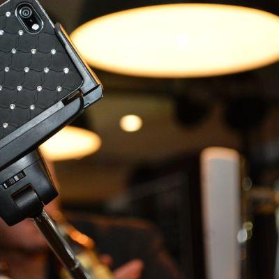 Juhlijat ottavat ravintolassa kuvaa itsestään älypuhelimen ja selfie-kepin avulla.