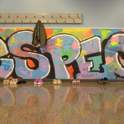 Respect-teksti kirjoitettuna graffitina Haukkavuoren koulun naulakoiden alle seinään Kotkassa.
