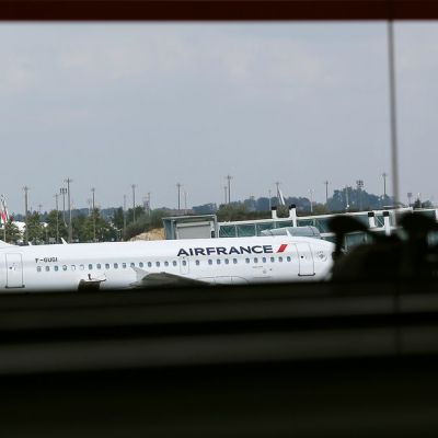 Nainen katselee tummennetun ikkunan läpi Charles de Gaullen lentokentälle. Edessä näkyy Air Francen lentokone, matkustaja on siluetissa.