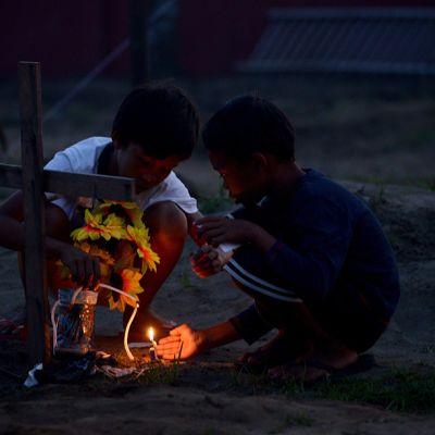 Pojat sytyttävät kynttilöitä joukkohaudalle.