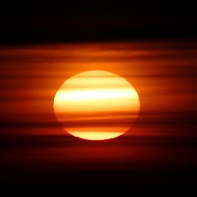 Aurinko punertavien pilvien takana