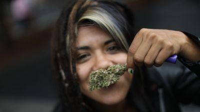 En ung kvinna med en liten mängd marijuana, deltog i en demonstration utanför Högsta domstolen då beslutet om cannabis fattades.