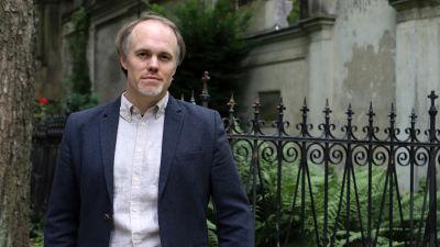 Sociologen Thorsten Benkel framför ett gravmonument.