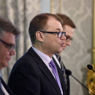 Yhteiskuvassa Timo Soini, Juha Sipilä ja Alexander Stubb. Sipilä pitää puhetta.
