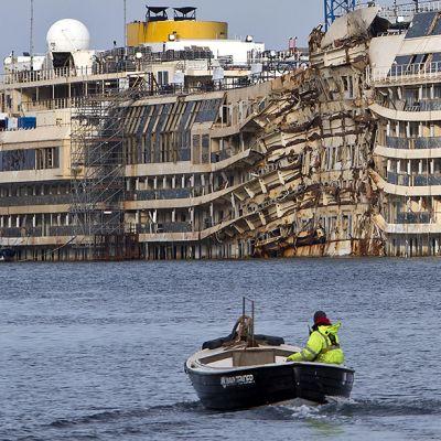 Pieni vene kulkee Costa Concordian ohitse.