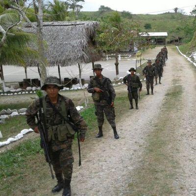 Joukko asepukuisia sotilaita kulkee tienviertä olkikatoksen ja suurten puiden ohi.