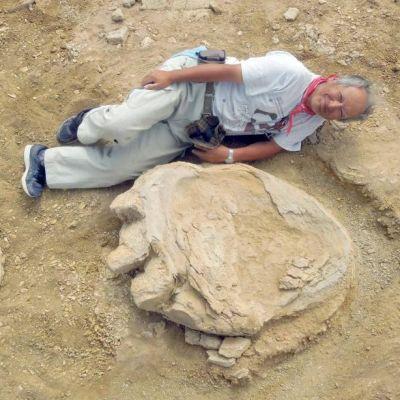Hymyilevä tutkija makaa koholle kivettyneen jalanjäljen vieressä.
