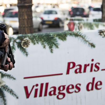 Kädet pitelevät asetta, valkoisessa kyltissä lukee Paris Villages de Noël.