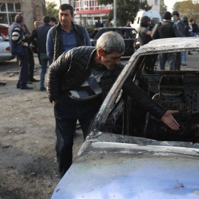 Mies katsastaa tuhoja Bardan kaupungin keskustassa tuhoutuneen auton vieressä.