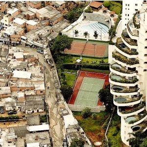 Eriarvoisuus Brasiliassa. Kuvassa köyhä Paraisopolisin favela ja aidan takana rikas naapurustoSao Paulossa ja aidan takana luksuskerrostalo uima-altaineen ja tenniskenttineen.