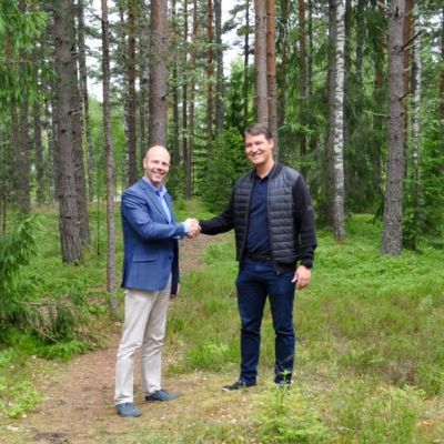 Två män står i en skogsdunge och skakar hand. Det är Sjundeås tekniska direktör Markus Moisio och Oskari Seppelvirta från byggbolaget Ki Oy Rovaniemen Sarkatupa.
