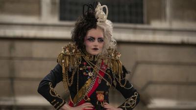 Cruella (Emma Stone) i bestämd med händerna i sidorna iklädd en punk/armé-inspirerad rock.