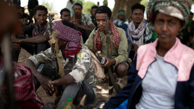 Soltaer som återvänt till ett läger sitter under ett träd och väntar. På plats finns också lokalbor som erbjuder mat- och sovplats.