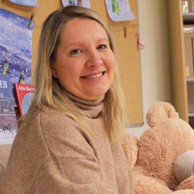 En kvinna i beige tröja sitteri en beige soffa bredvid en stor gosebjörn. Bakom henne syns teckningar på julgranar.