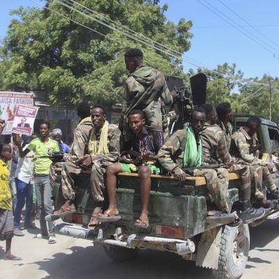 Sotilaita istuu kuvassa lava-auton lavalla. Auton ympärillä on siviilejä.