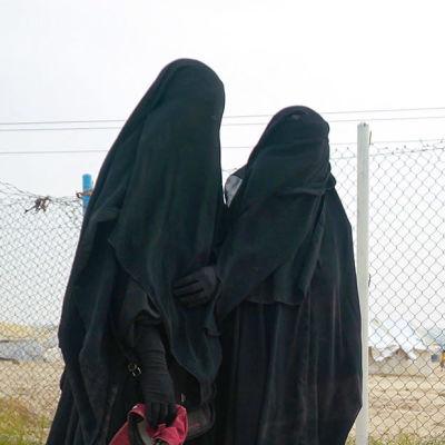 Två kvinnor står framför ett stängsel på lägret al-Hol i Syrien.