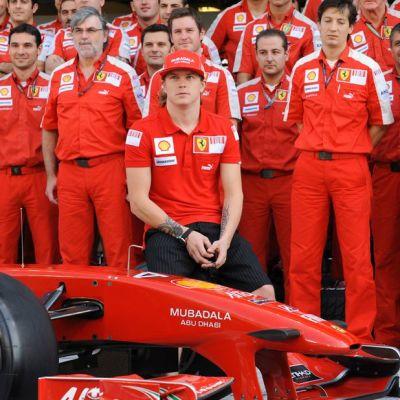 Kimi Räikkönen poseeraa Ferrari-auton ja tallin henkilökunnan kanssa.