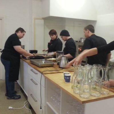 Nuoria laittamassa ruokaa ravintolan keittiössä.
