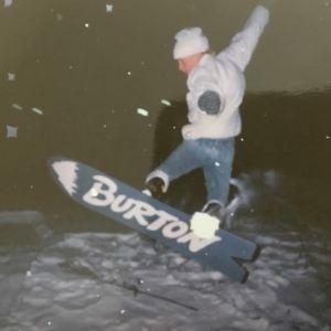 Farkkuihin ja valkoiseen talvitakkiin pukeutunut teini-ikäinen poika lumilautailee lumihangessa. Laudassa lukee Burton.