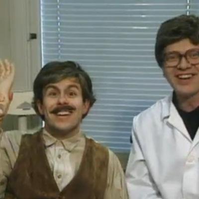 Lääkärin (Heikki Silvennoinen) vieressä istuva potilas Saarinen (Timo Kahilainen) heiluttaa irrallista tekokättä.
