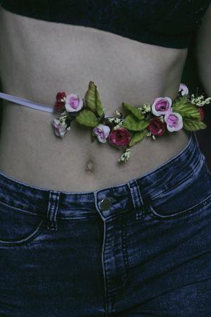naisella kukkanauha vyötärön ympärillä