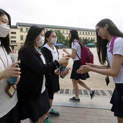 Opiskelijat desinfioivat käsiään ennen koululuokkaan menoa Etelä-Korean Soulissa.