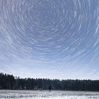 Tähdet näyttävät kiertävän kehää taivaalla, ihminen seisoo pellolla