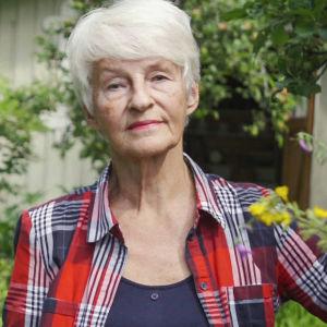 Äldre dam i kort, vitt hår och rutig skjorta står mitt i lummig trädgård med ena armen i sidan, med bestämd min.