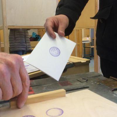Vaalilipuketta pudotetaan uurnaan Aleksanterin koululla