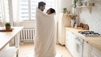 Man och kvinna stpr i ett kök insvepta i ett täcke och ler mot varandra