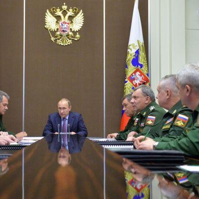 Vladimir Putin istuu pöydän päässä. Pöydän molemmin puolin istuu sotilaita.