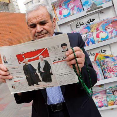 Mies pitää sanomalehteä käsissään.