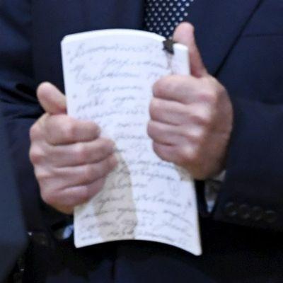 Muistiinpanot Putinin kädessä.