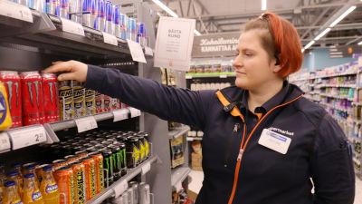 Butiksanställd iklädd blå uniform sorterar energidrycker vid en hylla i K-supermarket. I bakgrunden en skylt där det står att man inte säljer dryckerna åt under 15-åringar.