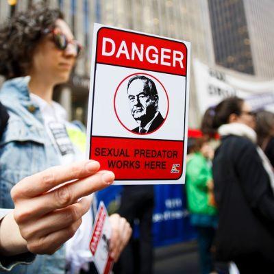 Nainen pitää kädessään korttia, jossa varoitetaan seksuaalisesta häiritsijästä