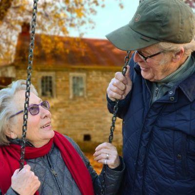 Vanha pariskunta katsoo hellästi toisiaan syksyisessä puutarhassa