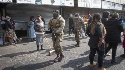 Sydafrikanska soldater patrullerar i förorten Alexandra utanför Johannesburg medan invånare städar upp efter kravaller som skakade området.
