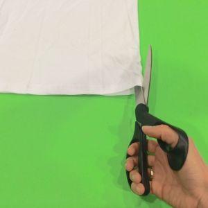 Lähikuva kädestä, jossa sakset, leikataan kangasta.